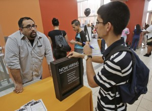 In this Tuesday, Oct. 6, 2015, photo, job applicant Lazaro Fonte, right, 24, of Miami, talks with Banana Republic assistant manager Edward Ortega, during a job fair at Dolphin Mall in Miami. The U.S. Labor Department reports on the number of people who applied for unemployment benefits during the week ending Oct. 3 on Thursday, Oct. 8, 2015. (AP Photo/Wilfredo Lee)