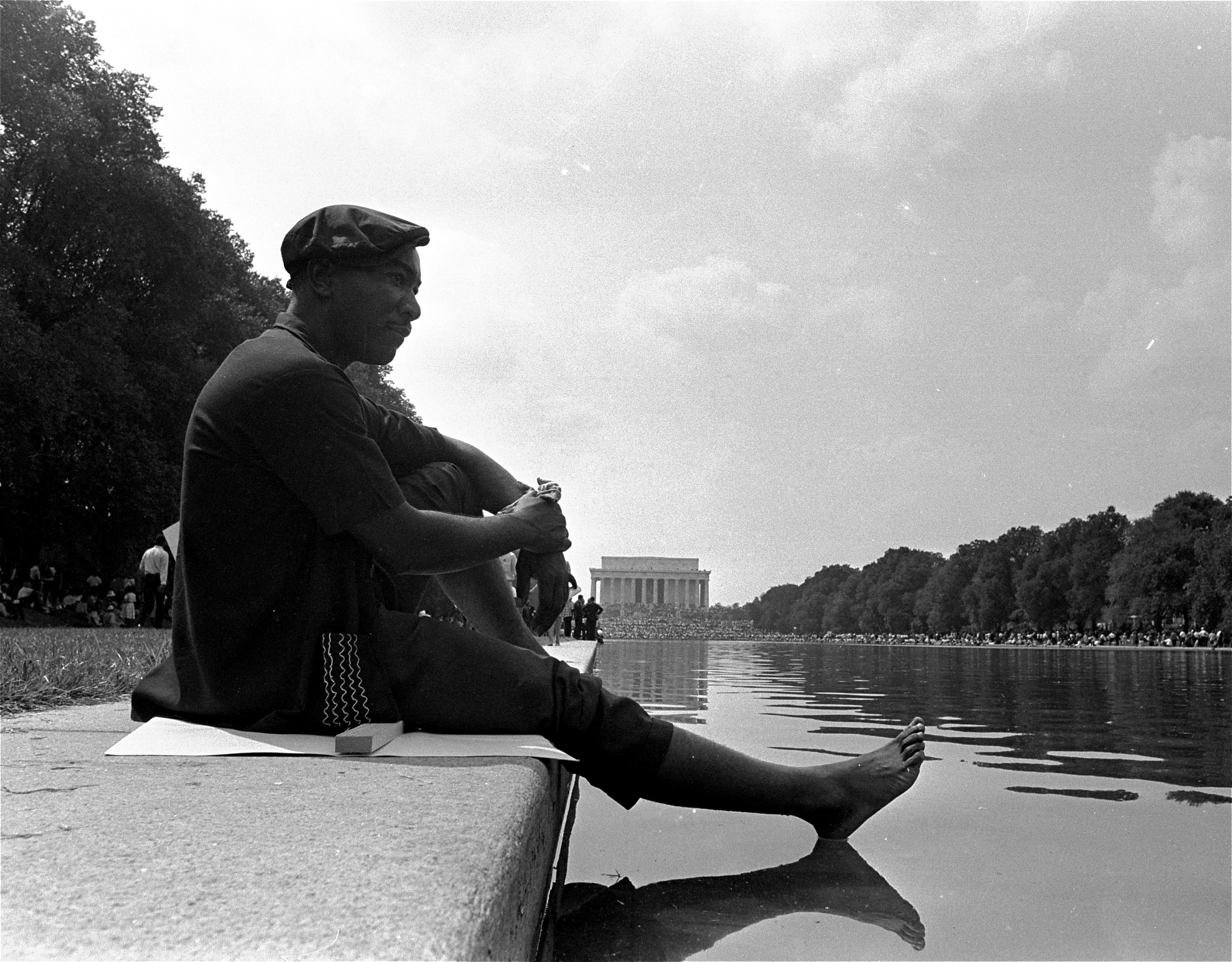 A civil rights marcher cools off his bare foot on the surface of the reflecting pool near the Lincoln Memorial following the March on Washington for Jobs and Freedom, August 28, 1963. (AP Photo)