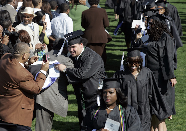 A student hugs family during the procession at commencement ceremonies at Hampton University in Hampton, Virginia. (AP Photo/Steve Helber)
