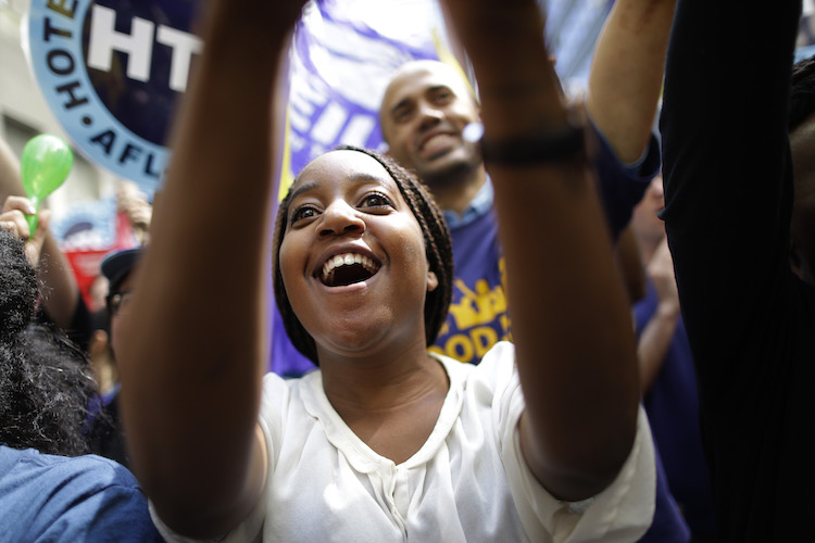 An activist cheers at a minimum wage rally in New York. Given the slow productivity growth, some economists are wondering if higher wages might increase productivity.