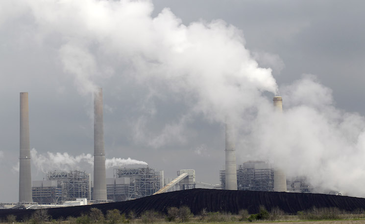 Exhaust rises from smokestacks in front of piles of coal at NRG Energy's W.A. Parish Electric Generating Station in Thompsons, Texas. (AP Photo/David J. Phillip)
