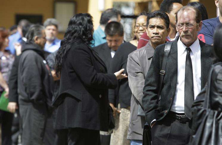 Job applicants wait in a long line at a job fair in San Jose, Calif.