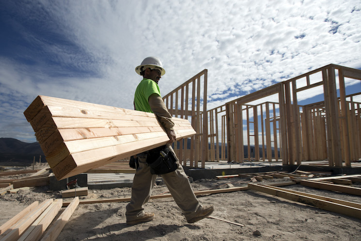 Construction worker Miguel Fonseca carries lumber as he works on a house frame for a new home in Chula Vista, Calif.