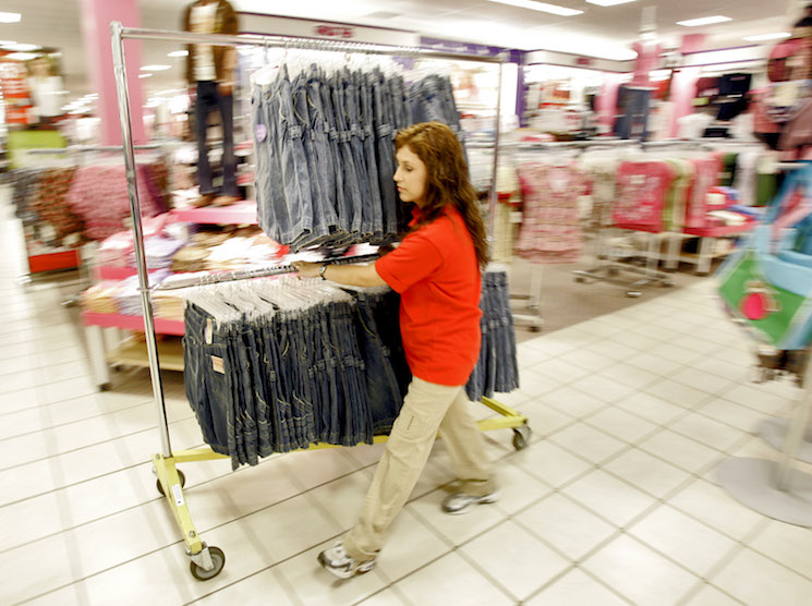 A retail employee wheels out a rack of girls' clothing in Phoenix.