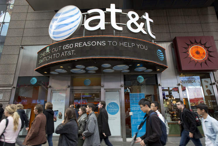 People walk by an AT&T retail store, Monday, Oct. 24, 2016, in New York. AT&T plans to buy Time Warner for $85.4 billion.