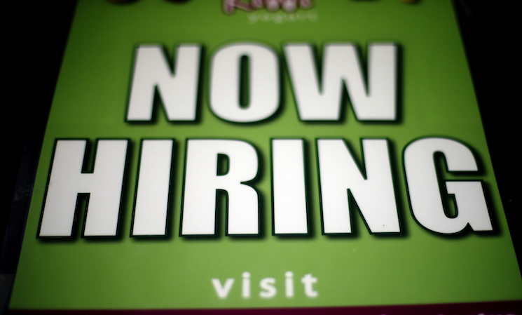 "A ""Now Hiring"" sign appears in a storefront display window in Philadelphia."