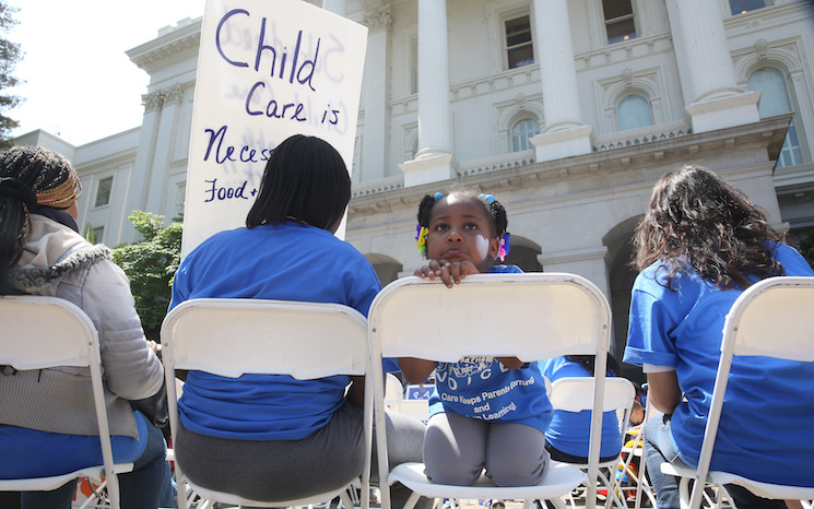 In this May 6, 2015, file photo Saryah Mitchell, sits with her mother, Teisa, Gay, left, a rally calling for increased child care subsidies at the Capitol in Sacramento, Calif. In much of the U.S., families spend more on child care for two kids than on housing. And if you're a woman, it's likely you earn less than your male colleagues even though one in four households with kids relies on mom as the sole or primary breadwinner.