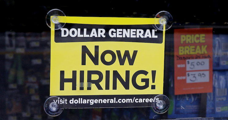 "A ""Now Hiring"" sign hangs in the window of a Dollar General."