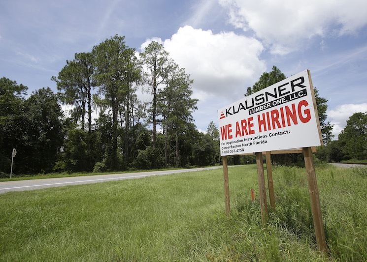 A sign along US 90 advertises job openings at the Klausner lumber mill in Live Oak, Fla.