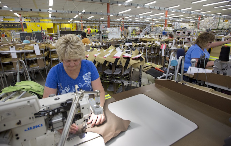Misty Thurston stitches suits for firefighters at Globe Manufacturing Co. in Pittsfield, N.H. A new paper looks at whether fluctuations in employers' revenue affects workers' earnings.