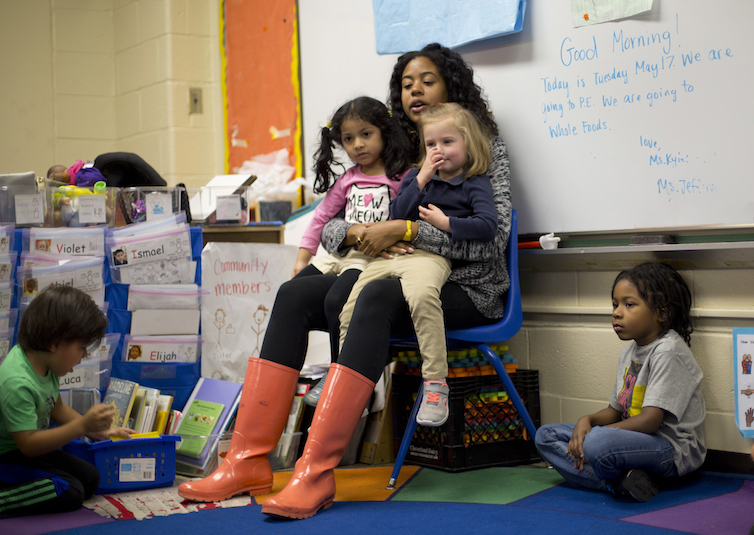Pre-K teacher Epernay Kyles, center, talks about class activities with her students.