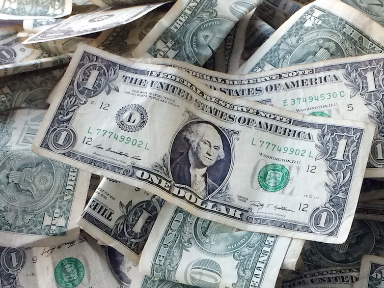 One dollar bills in a tip jar at a car wash in Brooklyn, NY.