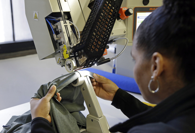 A woman works with fabric at 99Degrees Custom in Lawrence, Massachusetts.