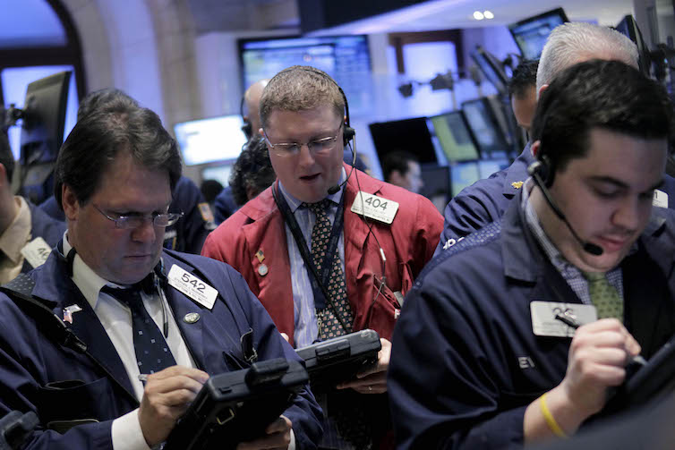 Traders work on the floor at the New York Stock Exchange in New York.