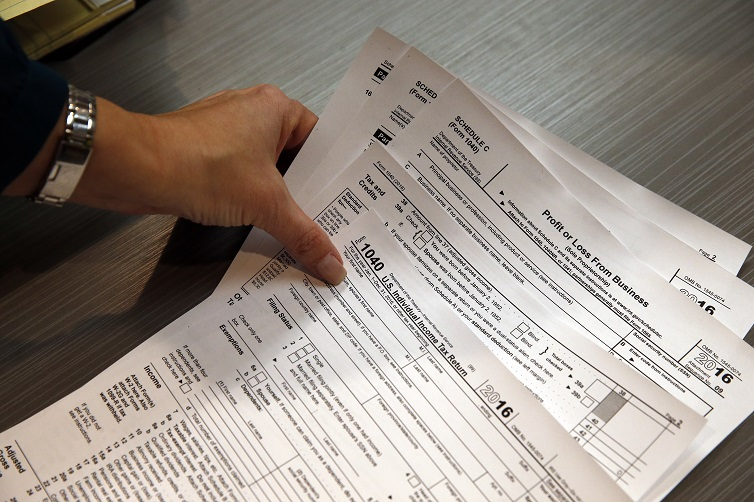 Tax professional and tax preparation firm owner Alicia Utley reaches for hard copies of tax forms.
