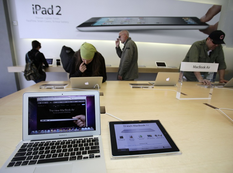 Customers look at the Apple MacBook Air and the iPad 2 at the Apple Store in San Francisco.