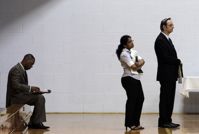 Job seekers wait in a line at a job fair in Southfield, Michigan.