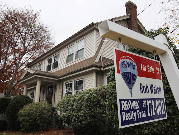 A for sale sign hangs in front of a home, in Milton, Massachusetts.