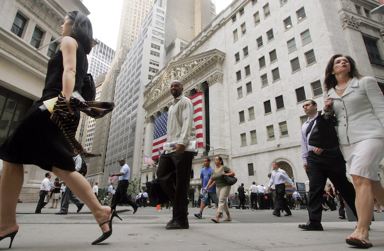 Men and women walk to work on Wall Street in New York.