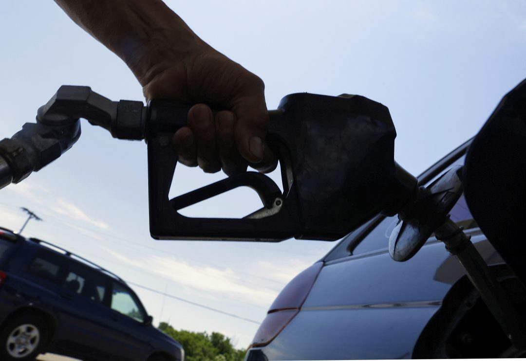 A motorist puts fuel in his car's gas tank at a service station in Springfield, Illinois, June 2013.