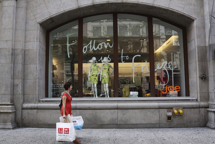 A shopper walks past a store on Fifth Avenue in New York.