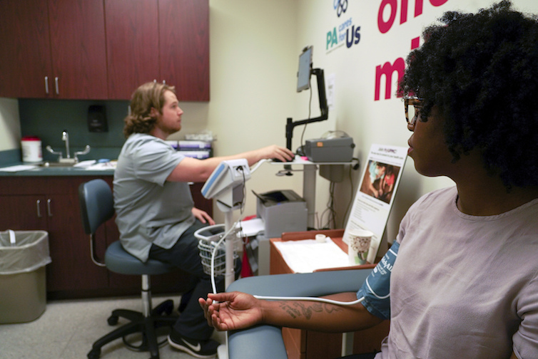 A research technician at the University of Pittsburgh Medical Center collects blood pressure data from a patient.