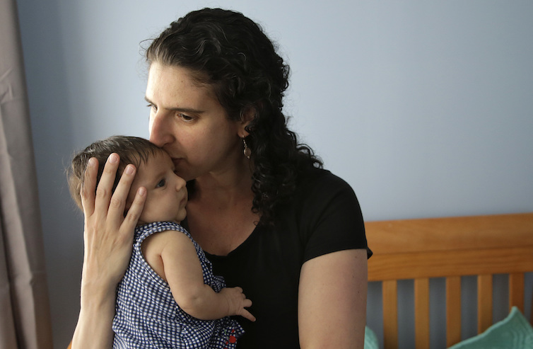 Elena Tenenbaum kisses her eight-week-old baby Zoe at their home in Providence, Rhode Island. Tenenbaum has been able to use Rhode Island's paid family leave program, which started in 2014 and covers four weeks of partial pay.