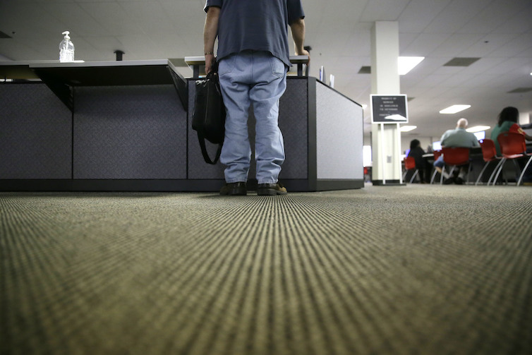 A lone job seeker checks in at the front desk of the Texas Workforce Solutions office in Dallas.