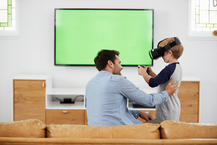 A father and son play with a virtual reality headset. A new study shows that sons are more likely to start their own businesses if their fathers are entrepreneurial.